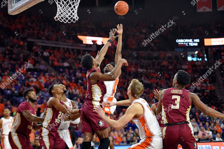 Clemson's John Newman lll, center right, shoots while defended by Florida State's Malik Osborne, center left, during the first half of an NCAA college basketball game, in Clemson, S.C