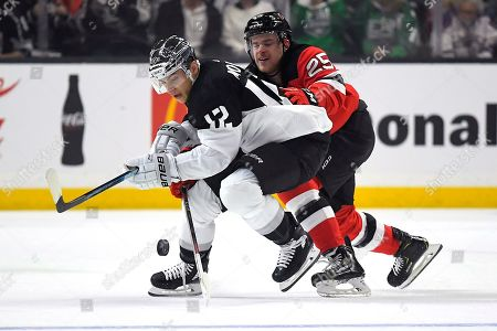 Los Angeles Kings center Trevor Moore, left, tries to move the puck while under pressure from New Jersey Devils defenseman Mirco Mueller during the first period of an NHL hockey game, in Los Angeles