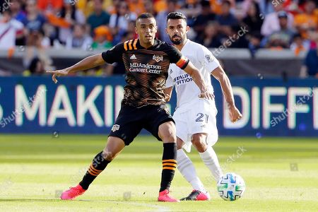 Houston Dynamo forward Mauro Manotas, left, moves the ball in front of Los Angeles Galaxy defender Giancarlo Gonzalez (21) during the second half of an MLS soccer match, in Houston