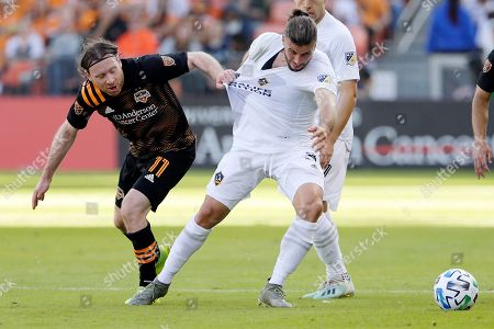 Houston Dynamo midfielder Tommy McNamara (11) pulls the jersey of LA Galaxy defender Emiliano Insúa (3) during the second half of an MLS soccer match, in Houston