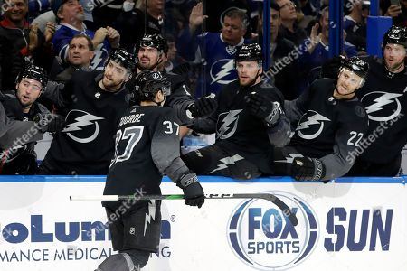 Tampa Bay Lightning center Yanni Gourde (37) celebrates with the bench after his goal against the Calgary Flames during the second period of an NHL hockey game, in Tampa, Fla