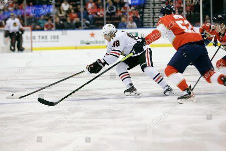 Nick Bjugstad, Patrick Kane, MacKenzie Weegar. Chicago Blackhawks right wing Patrick Kane (88) skates for the puck against Florida Panthers defenseman MacKenzie Weegar (52) during the first period of an NHL hockey game, in Sunrise, Fla