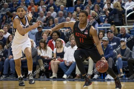Stock Image of San Diego State forward Matt Mitchell (11) drives past Nevada forward Robby Robinson (1) during the first half of an NCAA college basketball game in Reno, Nev