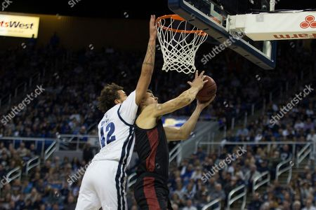 San Diego State forward Yanni Wetzell (5) is fouled as he shoots by Nevada forward K.J. Hymes (42) during the second half of an NCAA college basketball game at Lawlor Events Center in Reno, Nev