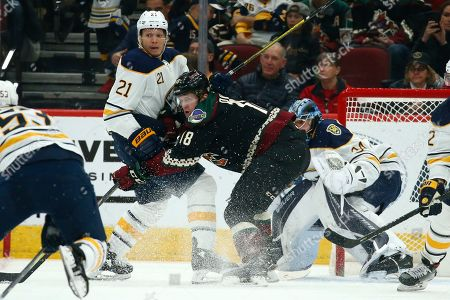 Arizona Coyotes center Christian Dvorak (18) and Buffalo Sabres right wing Kyle Okposo (21) battle for position during the second period of an NHL hockey game, in Glendale, Ariz. The Coyotes defeated the Sabres 5-2