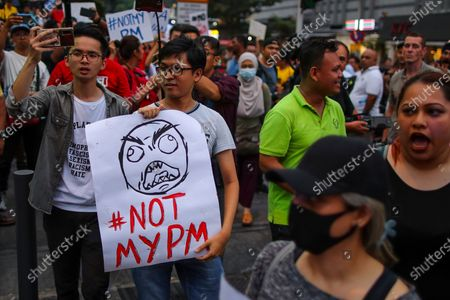 A protester holds a placard that reads '#NOTMYPM' during a demonstration to protest the ejection of the democratically elected government in Kuala Lumpur, Malaysia, 01 March 2020. The Yang di-Pertuan Agong (ruling monarch of Malaysia) Abdullah of Pahang named Muhyiddin the country's new premier on 29 February 2020 following the resignation of his predecessor, 94-year-old Mahathir Mohamad, a week earlier.
