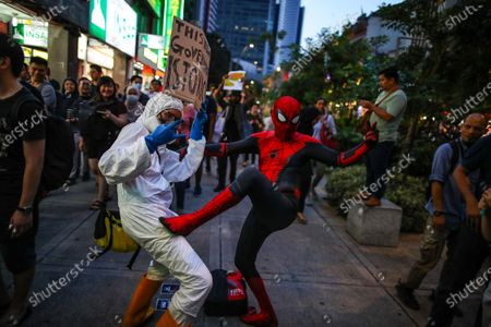 A protester wearing a protective suit (L) and another wearing a costume of the comic character 'Spiderman' (R) react during a demonstration to protest the ejection of the democratically elected government in Kuala Lumpur, Malaysia, 01 March 2020. The Yang di-Pertuan Agong (ruling monarch of Malaysia) Abdullah of Pahang named Muhyiddin the country's new premier on 29 February 2020 following the resignation of his predecessor, 94-year-old Mahathir Mohamad, a week earlier.