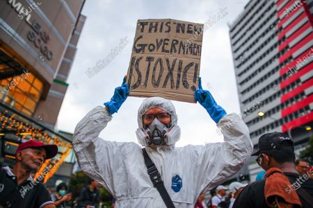 A protester wearing a protective suit holds a placard that reads 'THIS NEW GOVERNMENT IS TOXIC!' during a demonstration to protest the ejection of the democratically elected government in Kuala Lumpur, Malaysia, 01 March 2020. The Yang di-Pertuan Agong (ruling monarch of Malaysia) Abdullah of Pahang named Muhyiddin the country's new premier on 29 February 2020 following the resignation of his predecessor, 94-year-old Mahathir Mohamad, a week earlier.