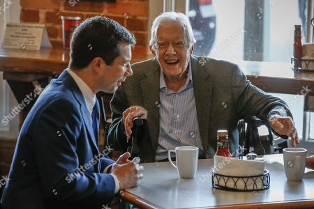 Democratic presidential candidate former South Bend, Ind., Mayor Pete Buttigieg, left, meets with former President Jimmy Carter, center, at Buffalo Cafe in Plains, Ga