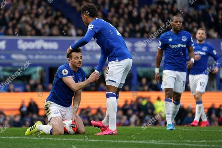 Everton's Mason Holgate congratulates teammate Leighton Baines, left, after he prevented a goal during the English Premier League soccer match between Everton and Manchester United at Goodison Park in Liverpool, England