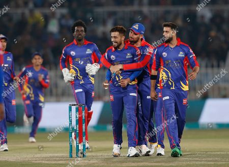 Karachi Kings pacer Mohammad Amir, center, celebrates with teammates after the dismissal of Islamabad United batsman Colin Munro during their Pakistan Super League T20 cricket match in Rawalpindi, Pakistan