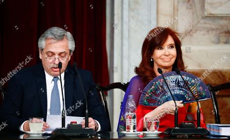 Argentina's President Alberto Fernandez, left, speaks as Vice President Cristina Fernandez de Kirchner uses a fan to keep cool as they open the 2020 session of Congress in Buenos Aires, Argentina