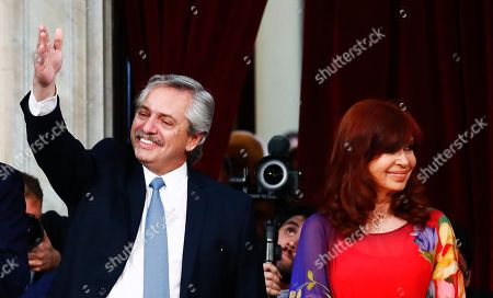 Argentina's President Alberto Fernandez, left, greets the crowd as he stands next Vice President Cristina Fernandez as he arrives to open the 2020 session of Congress in Buenos Aires, Argentina