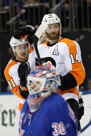 Philadelphia Flyers' Sean Couturier, right, celebrates his goal with Travis Konecny as New York Rangers goaltender Henrik Lundqvist reacts during the first period of the NHL hockey game, in New York