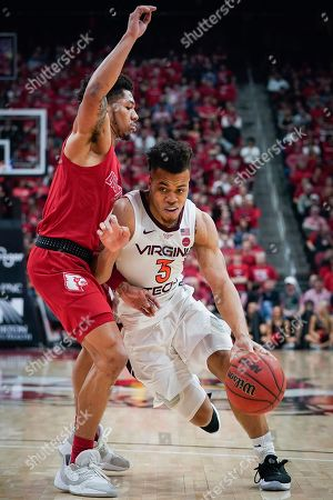 Stock Picture of Virginia Tech guard Wabissa Bede (3) dribbles around Louisville guard Lamarr Kimble (0) during the first half of an NCAA college basketball game, at the KFC YUM Center in Louisville, Ky