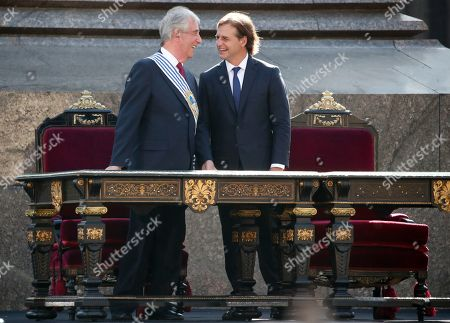 Uruguay's new President Luis Lacalle Pou, right, smiles with outgoing president Tabare Vazquez before receiving the presidential sash in Montevideo, Uruguay