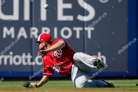 A ball hit for a single by New York Mets' Andres Gimenez bounces past Washington Nationals left fielder JB Shuck during the fourth inning of a spring training baseball game, in Port St. Lucie, Fla