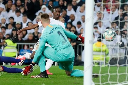 Stock Picture of Vinicius Junior, Marc-Andre ter Stegen. Real Madrid's Vinicius Junior, center right, scores his side's opening goal past Barcelona's goalkeeper Marc-Andre ter Stegen during the Spanish La Liga soccer match between Real Madrid and Barcelona at the Santiago Bernabeu stadium in Madrid, Spain