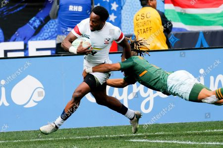 United States' Carlin Isles, left, is tackled by South Africa's Selvyn Davids during the Los Angels Sevens rugby tournament, in Carson, Calif