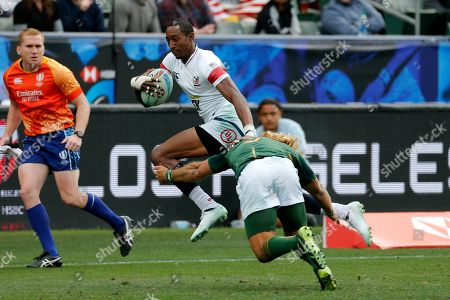 United States' Perry Baker, center, is tackled by South Africa's Muller Du Plessis, right, during the Los Angels Sevens rugby tournament, in Carson, Calif