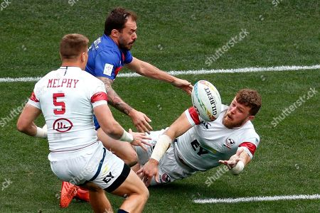Stock Picture of United States' Steve Tomasin, right, passes the ball to teammate Cody Melphy, left, while defended by France's Terry Bouhraoua during the Los Angels Sevens rugby tournament, in Carson, Calif
