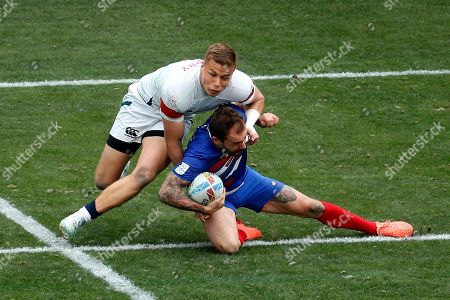 France's Terry Bouhraoua, right, id tackled by United States' Cody Melphy during the Los Angels Sevens rugby tournament, in Carson, Calif