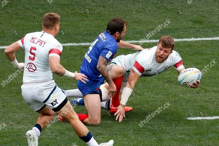 Stock Photo of United States' Steve Tomasin, right, passes the ball to teammate Cody Melphy, left, while defended by France's Terry Bouhraoua during the Los Angels Sevens rugby tournament, in Carson, Calif