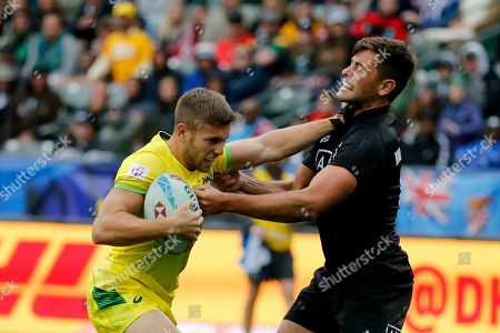 Australia's Josh Turner, left, is tackled by New Zealand's Andrew Knewstubb during the Los Angeles Sevens rugby tournament bronze final, in Carson, Calif. New Zealand won 21-19