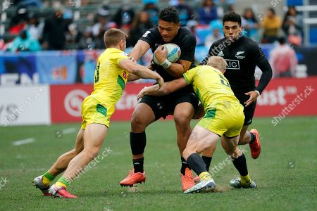 New Zealand's Calab Clarke, center, runs with the ball against Australia's Josh Turner, left, and Lachie Miller during the Los Angeles Sevens rugby tournament bronze final, in Carson, Calif. New Zealand won 21-19