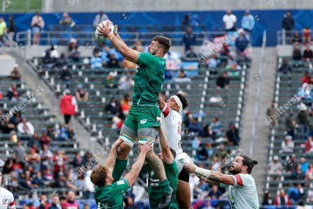 Stock Image of Ireland's Harry McNulty, left top, goes high for the ball over United States' Perry Baker during the Los Angeles Sevens rugby tournament 5th place play-off, in Carson, Calif. United States won 24-19