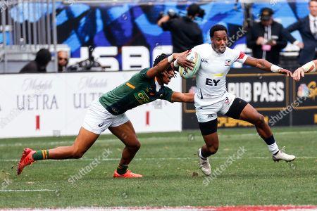 United States' Carlin Isles, right, is tackled by South Africa's Angelo Davids during the Los Angels Sevens rugby tournament, in Carson, Calif