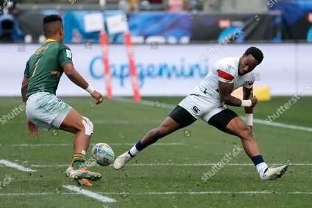 United States' Carlin Isles, right, loses the ball while defended by South Africa's Angelo Davids during the Los Angels Sevens rugby tournament, in Carson, Calif