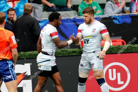 United States' Carlin Isles, left, is greeted by teammate Steve Tomasin after scored a try against South Africa during the Los Angels Sevens rugby tournament, in Carson, Calif