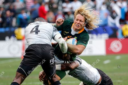 South Africa's Werner Kok, center, runs with the ball against Fiji's Asaeli Ratuvoka, left, and Kavekini Tabu during the Los Angeles Sevens rugby tournament final, in Carson, Calif. South Africa won 29-24 in overtime