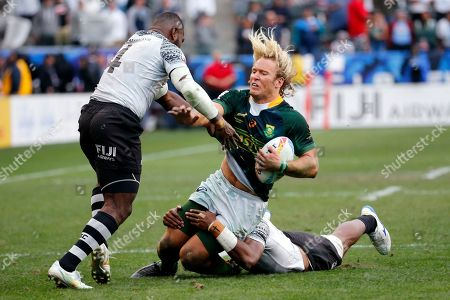 South Africa's Werner Kok, center, is tackled by Fiji's Asaeli Ratuvoka, left, and Kavekini Tabu during the Los Angeles Sevens rugby tournament final, in Carson, Calif. South Africa won 29-24 in overtime