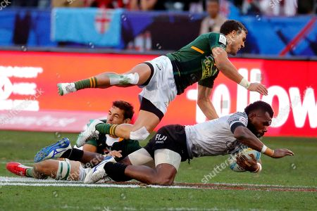South Africa's Muller Du Plessis, top, flies over Fiji's Kavekini Tabu, right bottom, during the Los Angeles Sevens rugby tournament final, in Carson, Calif. South Africa won 29-24 in overtime