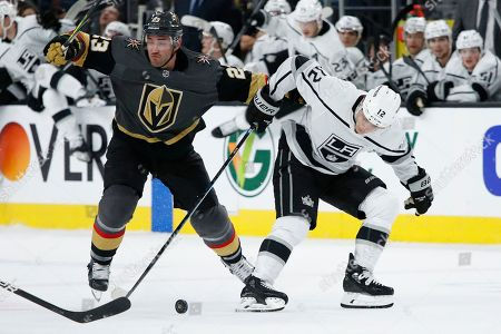 Los Angeles Kings center Trevor Moore (12) skates by Vegas Golden Knights defenseman Alec Martinez (23) during the third period of an NHL hockey game, in Las Vegas