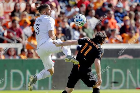 Stock Photo of Emiliano Insúa, Tommy McNamara. Los Angeles Galaxy defender Emiliano Insúa (3) jumps to bring down the ball next to Houston Dynamo midfielder Tommy McNamara (11) during the first half of an MLS soccer match, in Houston