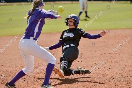 North Alabama's Mary Grayson Kilpatrick slides into third base as Evansville's Hannah Bassham (1) reaches for the ball an NCAA softball game against North Alabama on in Memphis, Tenn