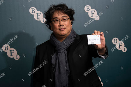 Bong Joon-ho poses for photographers upon arrival at the BFI Fellowship reception for actress Tilda Swinton at a central London hotel