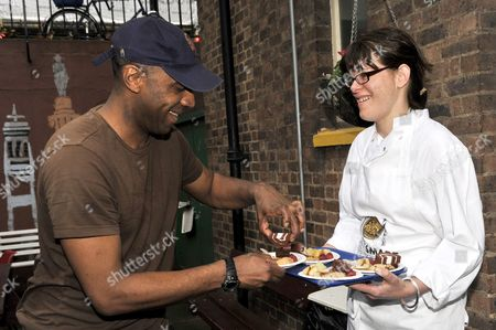 (L to R) Chef Anna Hansen serves food to a person using the shelter facilities