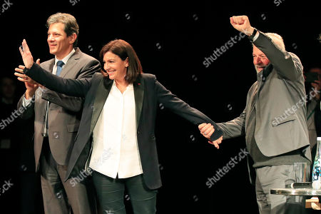 Paris mayor Anne Hidalgo, center, former Brazilian President Luiz Inacio Lula da Silva, right, and former Brazilian mayor of Sao Paulo Fernando Haddad acknowledge applauses during a meeting for the upcoming mayoral elections in Paris . France local elections starting March 15, 2020