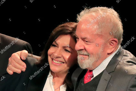 Paris mayor Anne Hidalgo, left, is hugged by former Brazilian President Luiz Inacio Lula da Silva, right, and former Brazilian mayor of Sao Paulo Fernando Haddad acknowledge applauses during a meeting for the upcoming mayoral elections in Paris . France local elections starting March 15, 2020
