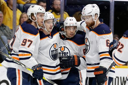 Edmonton Oilers right wing Josh Archibald, second from left, celebrates with Connor McDavid (97), Tyler Ennis (63) and Adam Larsson (6), of Sweden, after Archibald scored a goal against the Nashville Predators in the first period of an NHL hockey game, in Nashville, Tenn