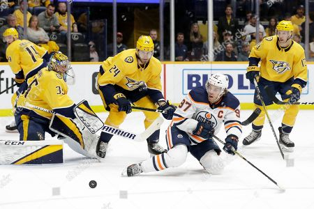 Edmonton Oilers center Connor McDavid (97) battles for the puck with Nashville Predators left wing Jarred Tinordi (24) as Predators goaltender Pekka Rinne (35), of Finland, guards the net in the first period of an NHL hockey game, in Nashville, Tenn