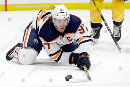 Edmonton Oilers center Connor McDavid reaches for the puck in the first period of an NHL hockey game against the Nashville Predators, in Nashville, Tenn