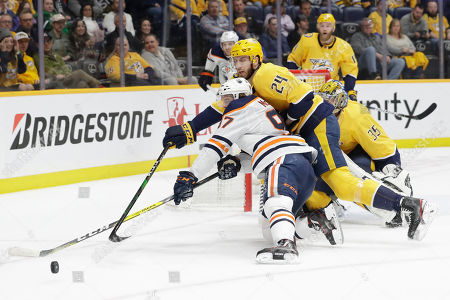 Edmonton Oilers center Connor McDavid (97) and Nashville Predators left wing Jarred Tinordi (24) reach for the puck in the first period of an NHL hockey game, in Nashville, Tenn