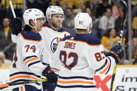 Edmonton Oilers center Leon Draisaitl (29), of Germany, celebrates with Ethan Bear (74) and Caleb Jones (82) after Draisaitl scored a goal against the Nashville Predators in the first period of an NHL hockey game, in Nashville, Tenn