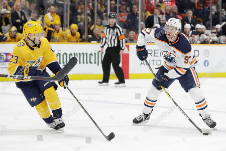 Edmonton Oilers center Connor McDavid (97) shoots and scores past Nashville Predators right wing Rocco Grimaldi (23) in the third period of an NHL hockey game, in Nashville, Tenn