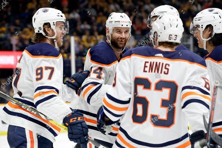 Edmonton Oilers right wing Zack Kassian (44) celebrates with Connor McDavid (97) and Tyler Ennis (63) after Kassian scored a goal against the Nashville Predators in the third period of an NHL hockey game, in Nashville, Tenn